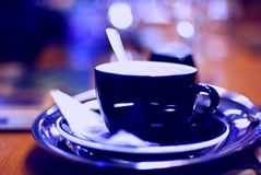 Coffee with milk. Black porcelain/china coffee cup and saucer with steaming milk coffee Royalty Free Stock Photography