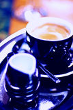 Coffee with milk. Black porcelain/china coffee cup and saucer with steaming milk coffee Stock Photo