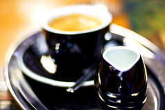 Coffee with milk. Black porcelain/china coffee cup and saucer with steaming milk coffee Stock Images