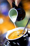Coffee with milk. Pouring milk in coffee in blue tone royalty free stock photos