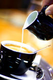 Coffee with milk. Pouring milk in coffee in blue tone stock photography