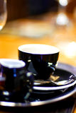 Coffee with milk. Black porcelain/china coffee cup and saucer with steaming milk coffee Royalty Free Stock Photo