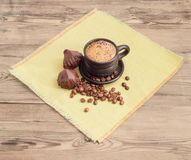Coffee with milk in black ceramic cup and chocolate truffles Royalty Free Stock Photo