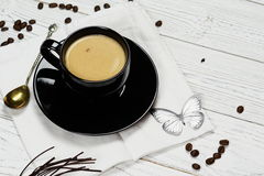 Coffee with milk. In a black cup on a white background Royalty Free Stock Image