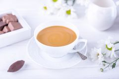 Coffee with milk, chocolate candies and chrysanthemums flowers on a white background royalty free stock image