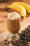 Coffee milk cocktail with banana on wooden background. Royalty Free Stock Photography