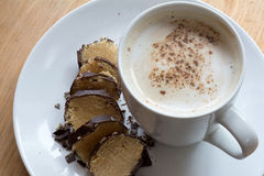 Coffee with milk foam and cocoa to marzipan in chocolate Royalty Free Stock Photo