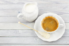 Coffee and milk jug on a wooden table Royalty Free Stock Photo