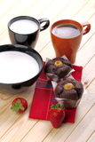 Coffee and milk with muffins and strawberries. Cup of coffee  and cup of milk with muffins and strawberries on a wooden countertop pine Royalty Free Stock Photo