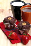 Coffee and milk with muffins  and strawberries. Cup of coffee and cup of milk  with muffins and strawberries on a wooden countertop pine Stock Photography