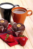 Coffee and milk with muffins and strawberries. Cup of coffee and cup of milk with muffins and strawberries on a wooden countertop pine Stock Images