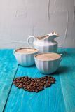 Coffee with milk, pour milk from the milkman, blue wooden backgr Royalty Free Stock Photography