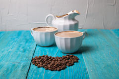 Coffee with milk, pour milk from the milkman, blue wooden backgr Stock Photo