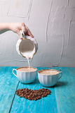 Coffee with milk, pour milk from the milkman, blue wooden backgr Stock Image