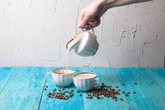 Coffee with milk, pour milk from the milkman, blue wooden background. Coffee beans Royalty Free Stock Image