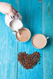 Coffee with milk, pour milk from the milkman, blue wooden background. Heart made of coffee beans Royalty Free Stock Photos