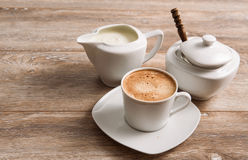 Coffee with milk and sugar on wooden table. Royalty Free Stock Images