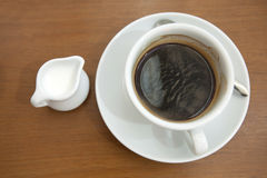 Coffee milk. Top view of a white cup of hot espresso coffee with steel spoon on white, isolate on white over grunge wood Stock Photo