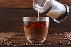 Coffee with milk in a transparent cup. Milk is poured into coffee on a wooden background Royalty Free Stock Images