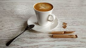 Coffee with milk in a white mug on a white table with sugar bags. stock photo