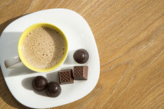 Coffee with milk on a white plate with chocolates Royalty Free Stock Image