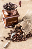 Coffee mill with aromatic coffee beans in sacking bag Stock Photography