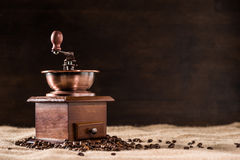 Coffee mill with aromatic coffee beans on scattered Stock Image