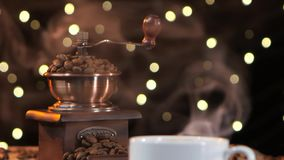 Coffee mill with beans. Closeup smoke with a white cup stock footage