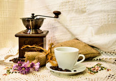 Coffee mill with burlap sack of roasted beans and white cup of coffee on the white knitted linen table-cloth Stock Photos