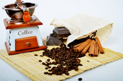 Coffee mill with cinnamon sticks on white royalty free stock photography