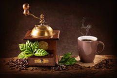 Coffee mill and a cup of coffee. Coffee mill with beans and green leaves and a cup of coffee Stock Photo