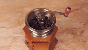 A coffee mill filled with coffee beans. Coffee grinder with coffee beans. In the kitchen on the marble table stock video