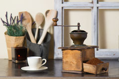 Coffee mill with freshly ground coffee. Old vintage manual coffee mill or grinder with a drawer full of freshly ground coffee beans standing on an old wooden Royalty Free Stock Photography