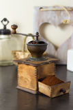 Coffee mill with freshly ground coffee. Old vintage manual coffee mill or grinder with a drawer full of freshly ground coffee beans standing on an old wooden Stock Image