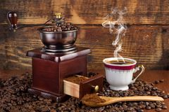 Coffee mill grinder and cup of coffee with smoke and wooden spoon on retro background royalty free stock photos