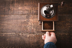 Coffee mill with hand on the wooden table horizontal Stock Images