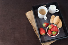 Coffee, mini French pastries and strawberries on wooden tray over black table. Black background Stock Images
