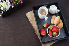 Coffee, mini French pastries and strawberries on wooden tray over black table. White and purple flowers in a decorative wooden cra Stock Photos