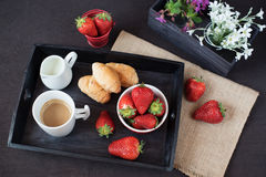 Coffee, mini French pastries and strawberries on wooden tray over black table. White and purple flowers in a decorative wooden cra Stock Images