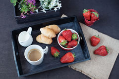 Coffee, mini French pastries and strawberries on wooden tray over black table. White and purple flowers in a decorative wooden cra Royalty Free Stock Photos