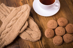 Coffee, mittens and oat cookie on wood Royalty Free Stock Image