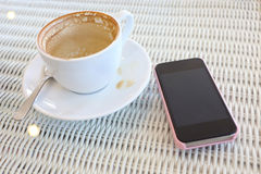 Coffee and mobile phone on white table in cafe Royalty Free Stock Photography