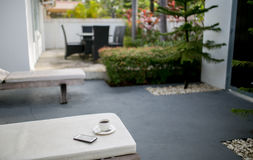 Coffee and MobilePhone on a Chair with pool in resort Royalty Free Stock Photos