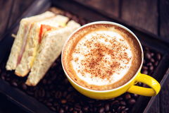 Coffee mocha hot and sandwiches on wooden table. Coffee mocha hot and coffee beans on wooden table on brown background Royalty Free Stock Images