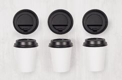 Coffee mockup - set of three white paper cups and blank black caps on white wood board, top view. Modern elegant concept for branding identity, advertising stock images