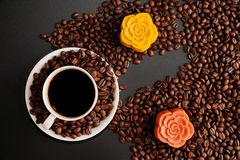 Coffee and colorful Chinese mooncakes on the coffee beans with black background. View of a cup of black coffee and colorful Chinese mooncakes on the coffee beans royalty free stock photography