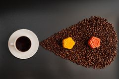 Coffee and colorful Chinese mooncakes on the coffee beans with black background. View of a cup of black coffee and colorful Chinese mooncakes on the coffee beans stock photo