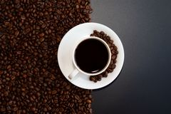 Black coffee and coffee beans with black background. View of a cup of black coffee and colorful Chinese mooncakes on the coffee beans with black background stock photography