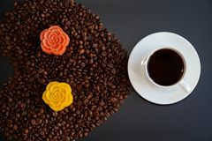 Black coffee and colorful Chinese mooncakes on the coffee beans with black background. View of a cup of black coffee and colorful Chinese mooncakes on the coffee royalty free stock image