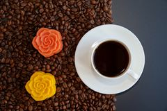 A cup of black coffee and colorful Chinese mooncakes on the coffee beans with black background. View of a cup of black coffee and colorful Chinese mooncakes on royalty free stock photo